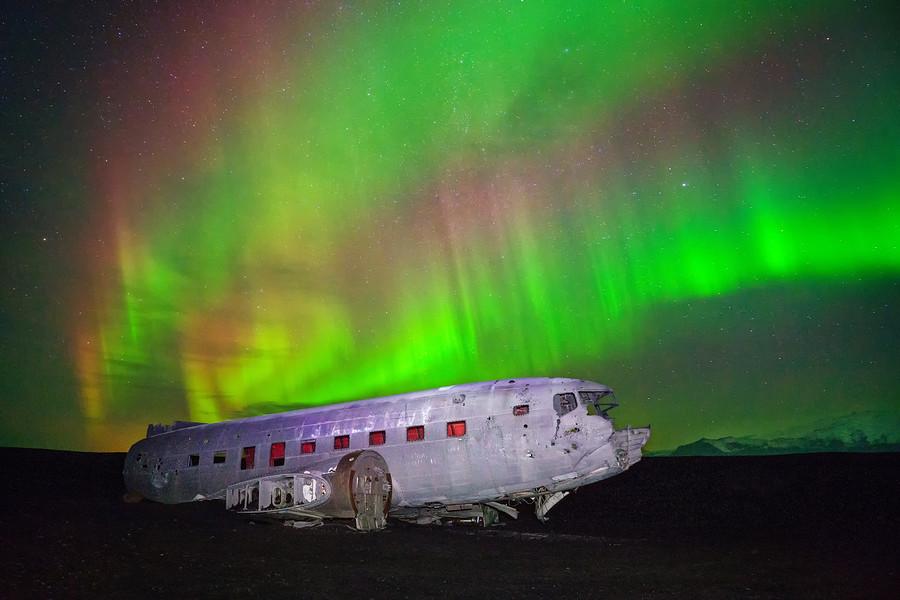 Islande, Solheimasandur. Carcasse d'un avion écrasé, sous une aurore boréale