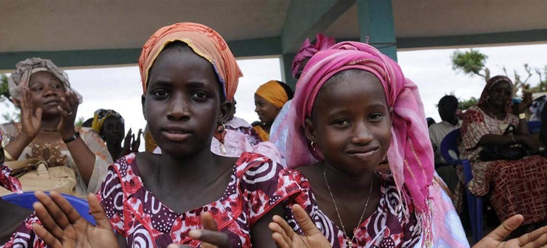 Deux jeunes filles au Sénégal applaudissent lors d'une célébration de l'abandon de la mutilation génitale féminine par plusieurs villages des environs
