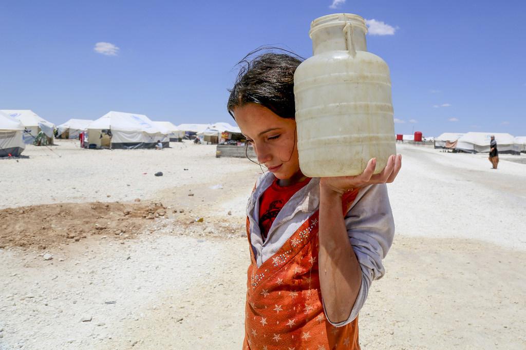 Horriya, 12 ans, porte un jerrycan d'eau en Syrie