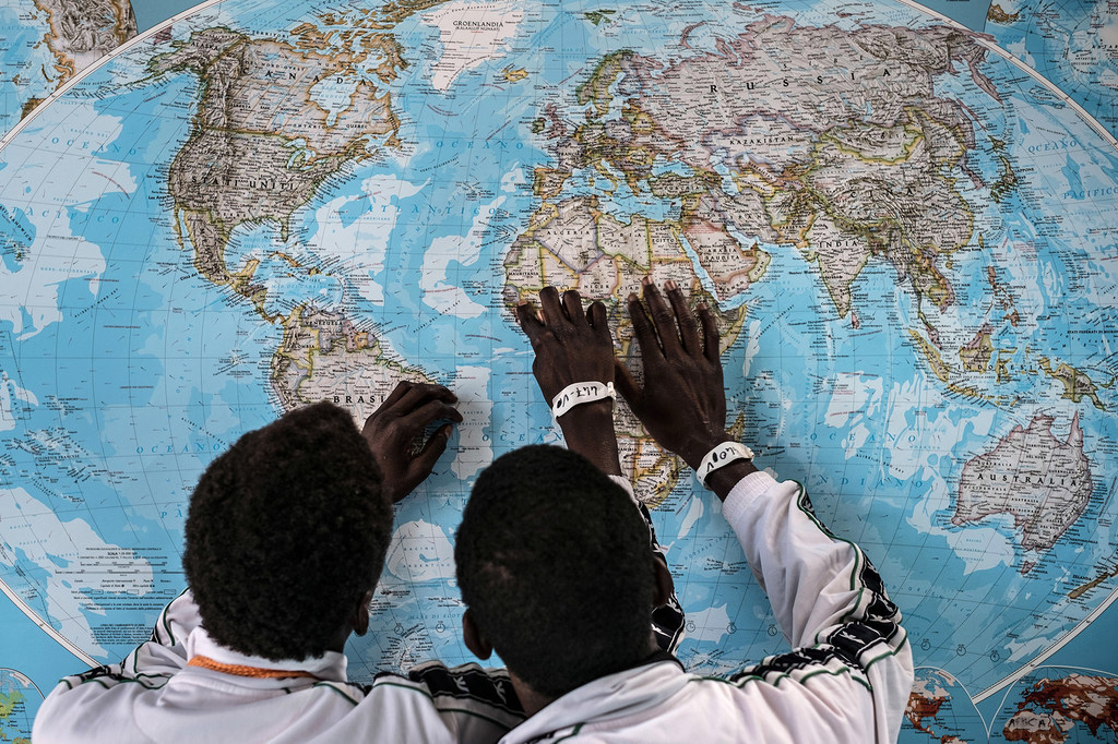 Deux jeunes migrants gambiens regardent une carte du monde