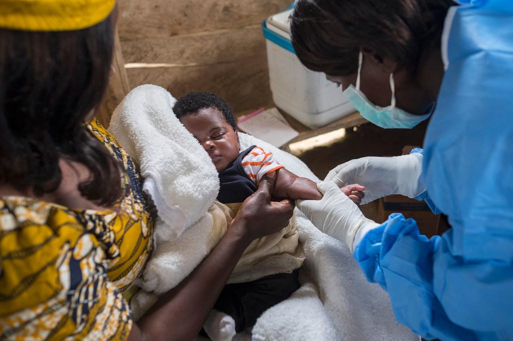 Une infirmière se prépare à vacciner un nourrisson